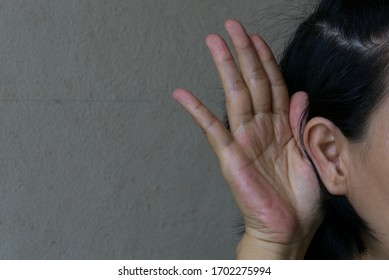 Woman tried to listen to the sounds around her. The lady was listening to is not clear. She cupped a hand to her ear to the voice more clearly.