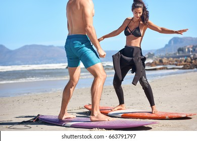 Woman tries to balance on surfboard during her private surf class lesson, adventurous active lifestyle