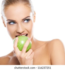 Woman tries to bite a fresh green apple, she is isolated on white