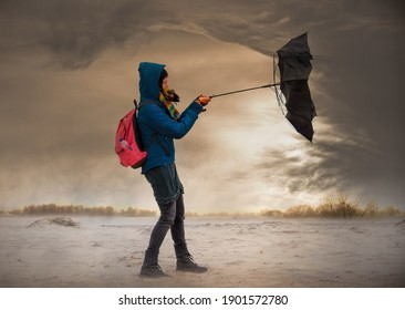 A woman tries to hold onto her umbrella during a strong storm. Impending storm clouds are looming over the vast landscape.