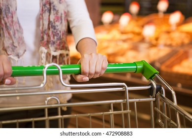 Woman with trolley buying fresh bread in bakery