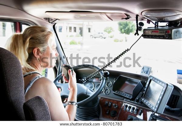 Woman truck driver in a big rig talking on the C.B. radio.