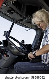 Woman truck driver getting out her log book and getting ready to start her trip.
