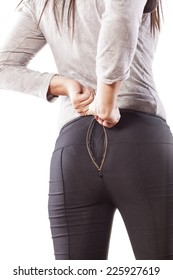 woman trying to close open and defective zip on her buttocks