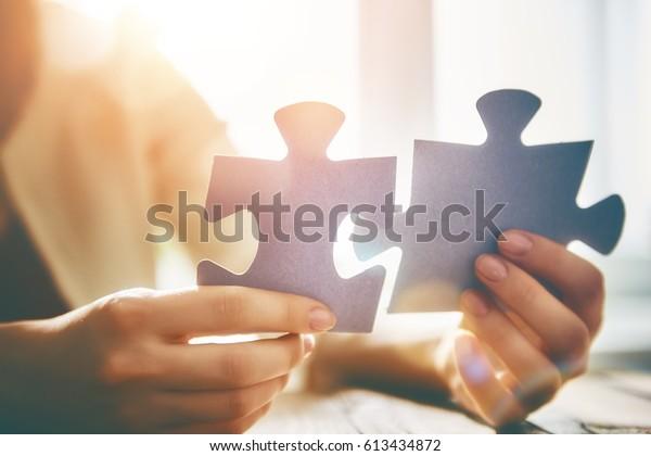 Frau versucht ein paar Puzzleteile miteinander zu verbinden. Vereinigungszeichen und Verbindungszeichen. Konzept der Geschäftsstrategie.
