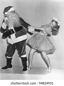 Woman trying to dance with Santa Claus
