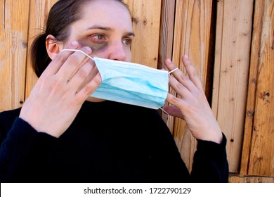 A woman is trying to hide traces of domestic violence by wearing a medical mask. The concept of rising domestic violence during quarantine isolation COVID-19.