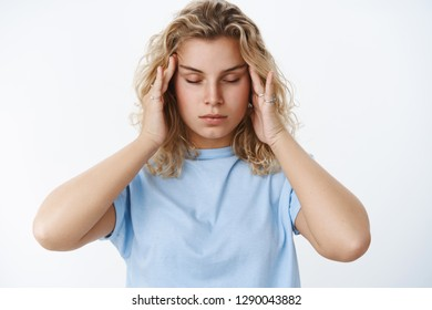 Woman trying keep emotions under control feeling distressed and drained massaging temples with fingers and close eyes to relax and focus, having headache or migraine over white background