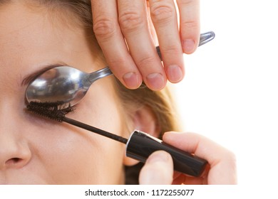 Woman trying new beauty viral trend. Woman applying mascara on eyelashes using small spoon.
