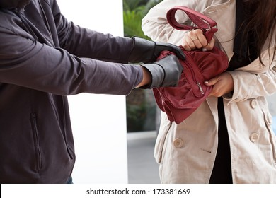 A woman trying not to let a man take her bag