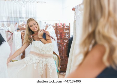 Woman trying on a dress in front of mirror in tailor shop