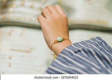 Woman trying on golden bracelet in the jewelry shop.