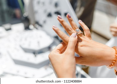 A woman trying on her new ring at outdoor flea handmade market, jewelry and shopping concept