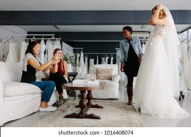Woman trying on wedding dress with female friends having fun and taking photographs.
