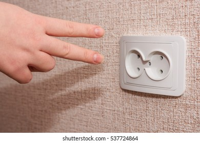 Woman trying to plug in her fingers into the double socket