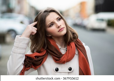 Woman trying to remember Closeup portrait headshot  young lady girl scratching head thinking daydreaming deeply about something looking up isolated cityscape outdoor background Multicultural mixt race