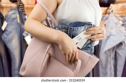 woman trying to steal trousers from a clothing store