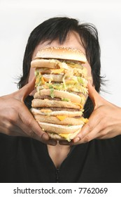 A woman trying to take a bite out of an oversized burger