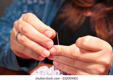 Woman  trying to thread a needle, close up