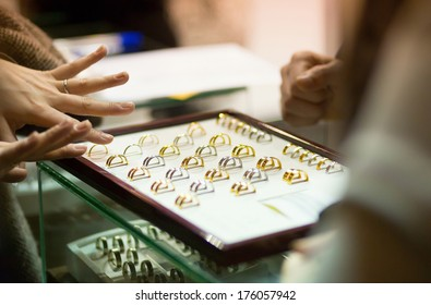 Woman trying wedding rings at a jeweller, focus on rings