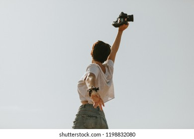 Woman in t-shirt jumping in her back outdoors, with a camera in the hand.