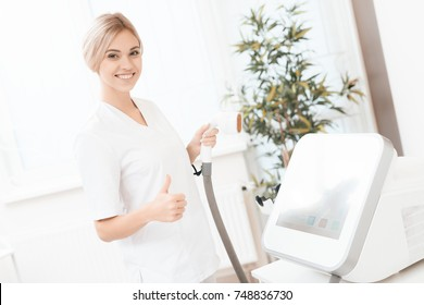 A woman tunes a laser hair removal machine. She holds a working part of the epilator in her hands and poses for a photo. It is located in a modern beauty salon.