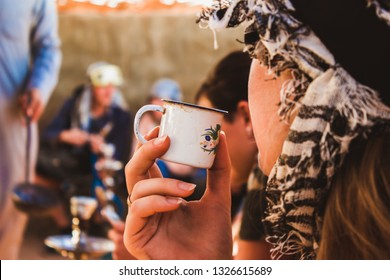 Woman with turban drinking Bedouin black tea in Arabic desert in Egypt.