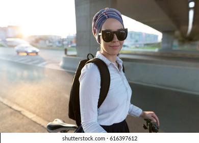 Woman with a turban riding a bike. Woman enjoying her free time doing sports.