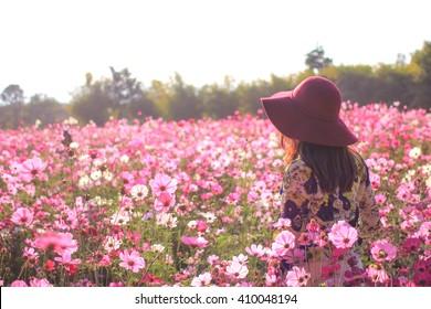 woman turn back wear red hat enjoying summer in pink flower field at sunlight