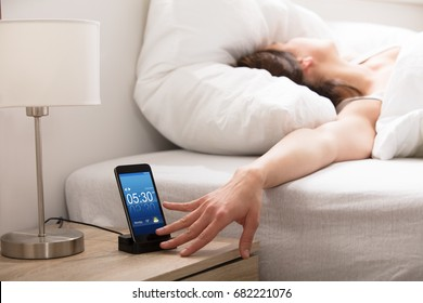 Woman Turning Off The Alarm On Cell Phone While Waking Up In The Morning