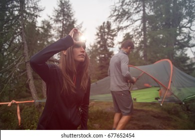 Woman turning on headlamp flashlight near hanging tent camping. Group of friends people summer adventure journey in mountain nature outdoors. Travel exploring Alps, Dolomites, Italy.