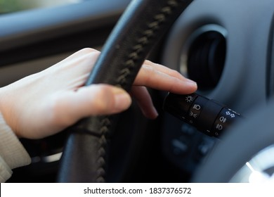Woman turning on left signal switch, close up shot of her hand. Car interior details.