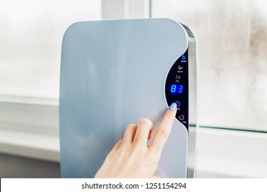 Woman turns dehumidifier on using touch panel by wet window. Humidity indicator shows high level of dampness in flat