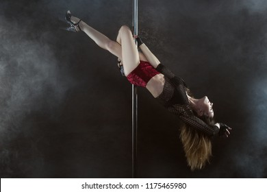 Woman turns on a pylon, she dances a striptease.