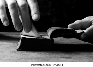 Woman turns the page in an old little bible or book, black and white background