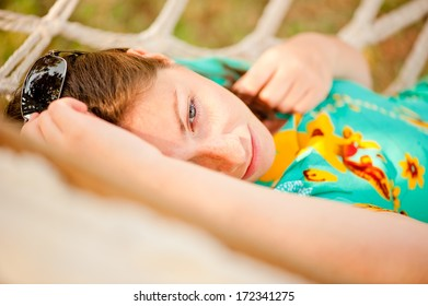 woman in a turquoise dress resting in a hammock