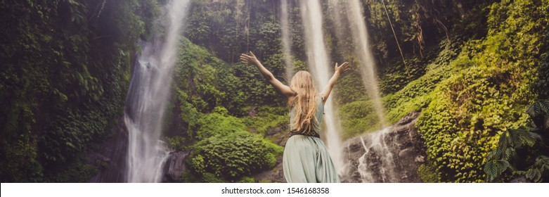 Woman in turquoise dress at the Sekumpul waterfalls in jungles on Bali island, Indonesia. Bali Travel Concept BANNER, LONG FORMAT