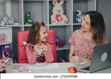 Woman tutor or foster parent mum helping cute caucasian school child girl doing homework sitting at kitchen table. Diverse nanny and kid learning writing in notebook studying at home.
