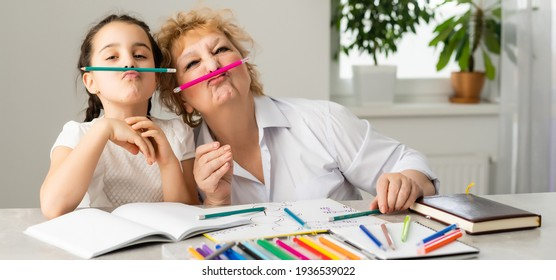 Woman tutor or foster parent mum helping cute caucasian school child girl doing homework sitting at table. Diverse nanny and kid learning writing in notebook studying at home.