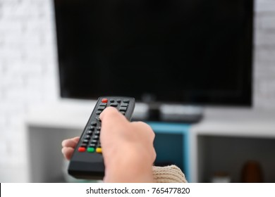 Woman with TV remote control switching channels, closeup