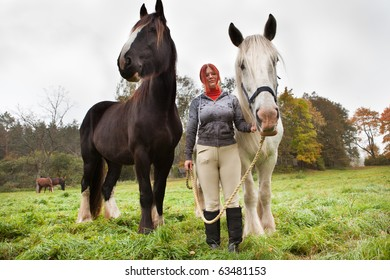 Woman with two big black and white horses in pasture