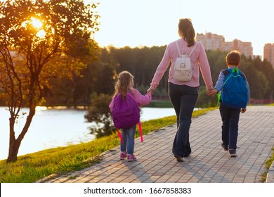 Woman and two children from back. mother accompanies the students along way. children with briefcases go from school, holding his mother's hand. friendly family go to preschool. meets from school