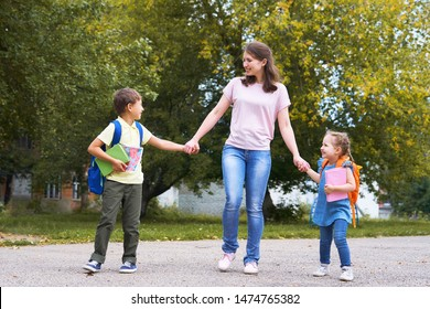a woman and two children are holding hands. mother accompanies students to school. children with school bags go to school. friendly family goes to kindergarten.happy children with a caring mother