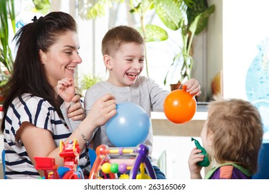 woman with two children playing with balloons in home interior laughter