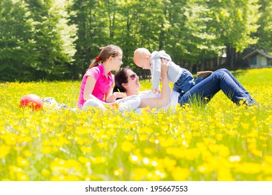 Woman with two cute kids on the park in spring, selective focus