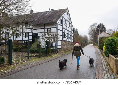 A woman with two dogs walks along the Limburgish village, the Netherlands