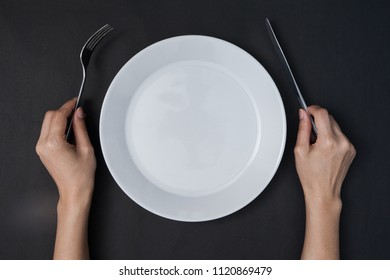 woman two hands hold a knife and fork and white dish on black background