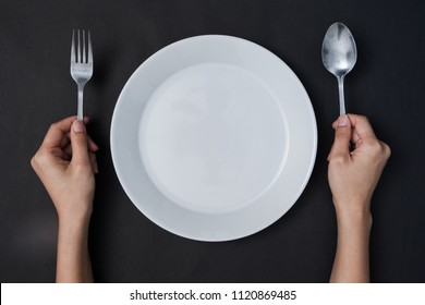 woman two hands hold a spoon and fork and white dish on black background