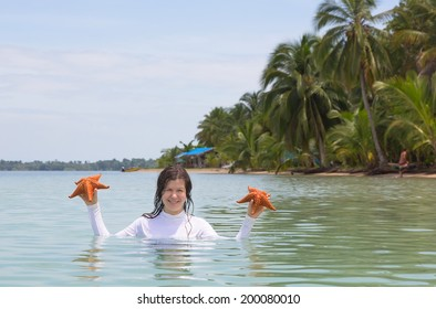 Woman with two starfish in hands, archipelago Bocas del Toro, Panama