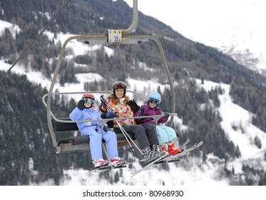 Woman and two young children on a chairlift at ski resort